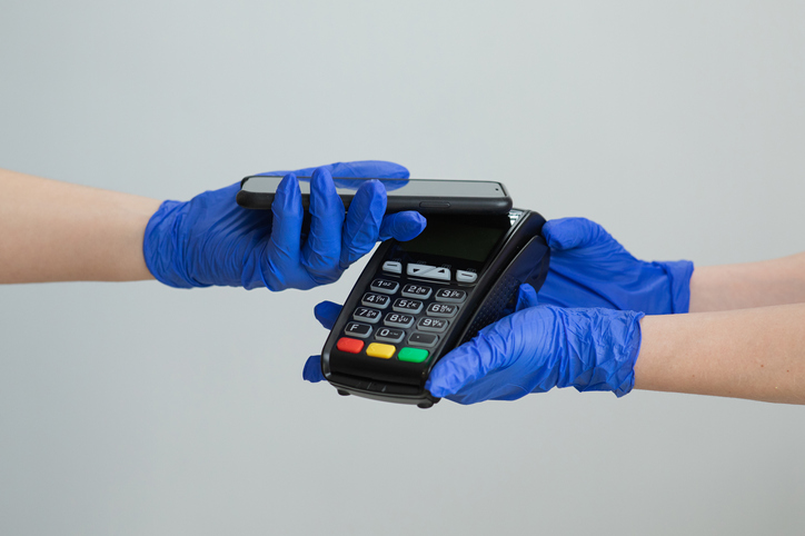 Card machine handled with protective rubber gloves